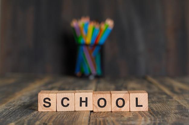 Concepto de regreso a la escuela con cubos de madera, lápices en soporte en vista lateral de la mesa de madera.