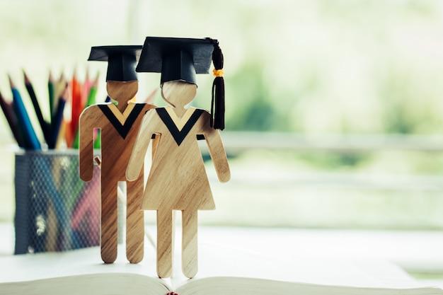 Concepto de regreso a la escuela, dos personas firman madera con graduación celebrando una gorra en un libro de texto abierto