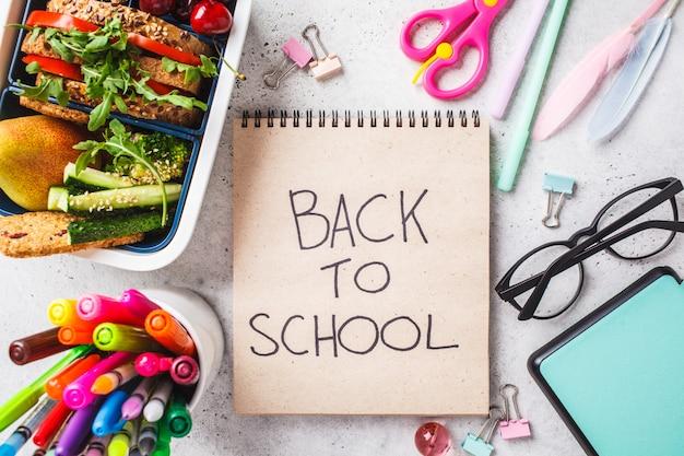 Concepto de regreso a la escuela con fiambrera con sandwich, frutas, bocadillos, cuaderno, lápices y artículos escolares