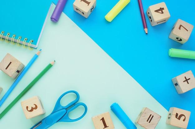 Concepto de regreso a la escuela, fondo creativo con útiles escolares y bloques de madera con números.