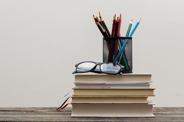 Concepto de regreso a la escuela con gafas, libros, lápices en soporte en vista lateral de madera y pared blanca.