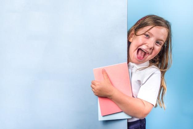 Concepto de regreso a la escuela. invitación a la escuela, banner publicitario. linda chica estudiante de primaria en uniforme clásico azul blanco, con libros, cuadernos. espacio de copia de fondo azul brillante colorido