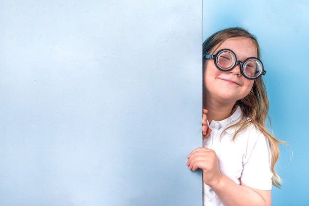 Concepto de regreso a la escuela. invitación a la escuela, banner publicitario. linda colegiala estudiante de primaria en uniforme clásico azul blanco, gafas divertidas. espacio de copia de fondo de moda azul brillante colorido