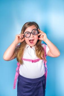 Concepto de regreso a la escuela. invitación a la escuela, banner publicitario. linda colegiala estudiante de primaria en uniforme clásico azul blanco, con mochila de libros, gafas divertidas. espacio de copia de fondo azul colorido