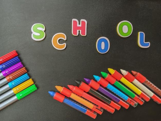 Concepto de regreso a la escuela. lápices de colores sobre fondo negro con la palabra escuela.