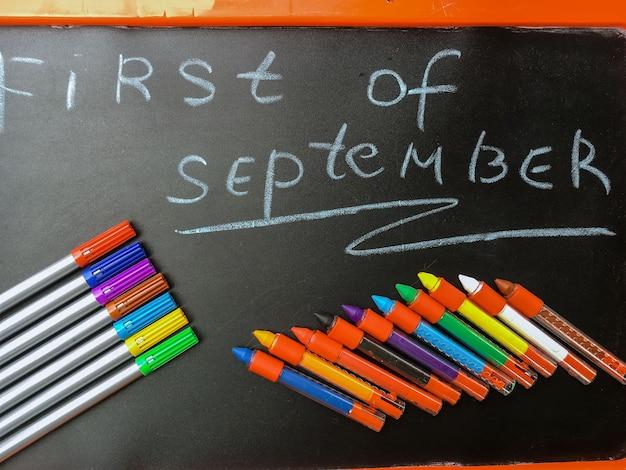 Concepto de regreso a la escuela. lápices de colores sobre fondo negro con las palabras primero de septiembre.