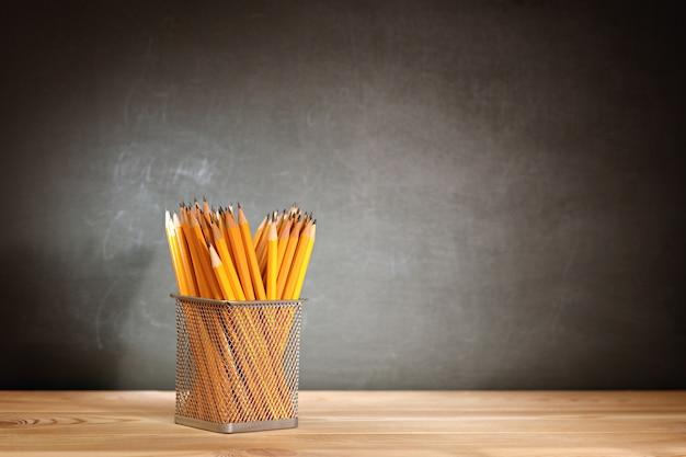 Concepto de regreso a la escuela. lápices sobre un pupitre de madera delante de una escuela de pizarra negra.