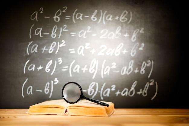 Concepto de regreso a la escuela. libros antiguos y lupa acostado en un pupitre de madera delante de una pizarra negra con fórmulas matemáticas de la escuela.