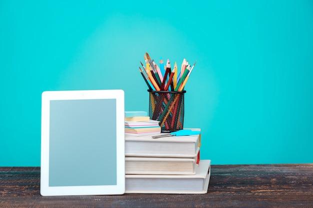 Concepto de regreso a la escuela. libros, lapices de colores y laptop