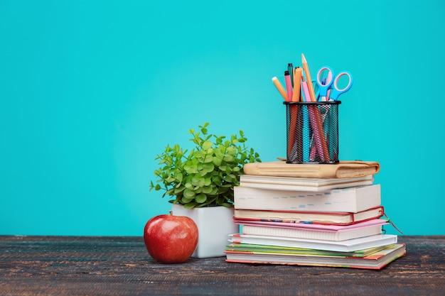 Concepto de regreso a la escuela. libros, lapices de colores y manzana