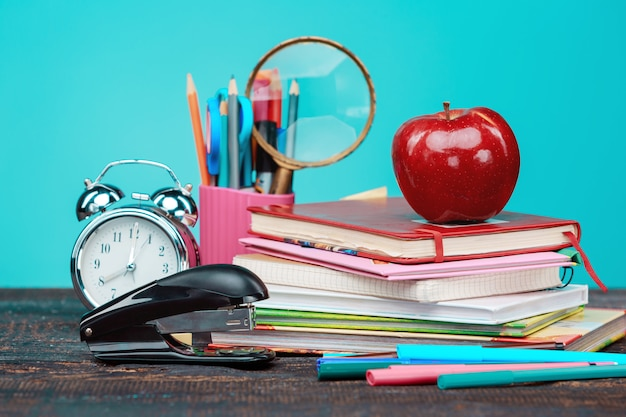 Concepto de regreso a la escuela. libros, lápices de colores y reloj.