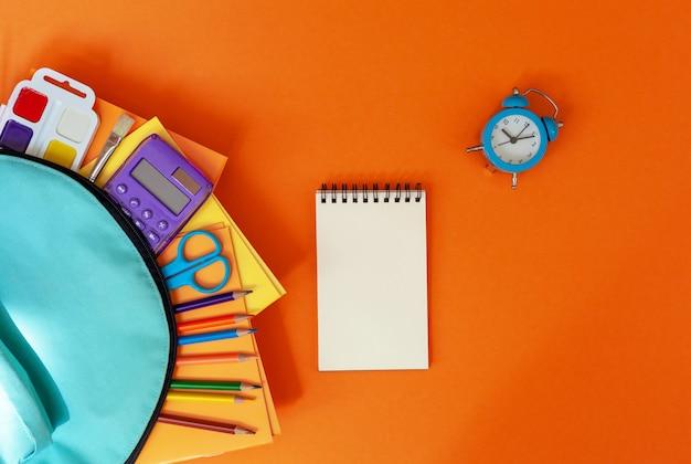 Concepto de regreso a la escuela. mochila escolar turquesa completa con suministros en naranja. piso laico.