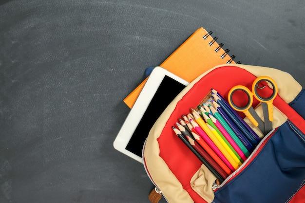 Concepto de regreso a la escuela. mochila con útiles escolares, tableta y contra pizarra. vista superior. copia espacio