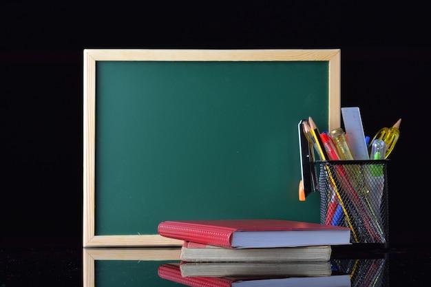 Concepto de regreso a la escuela con papelería en la mesa frente a la pizarra