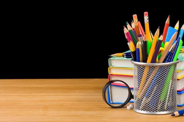 Concepto de regreso a la escuela y pila de libros aislados sobre fondo negro
