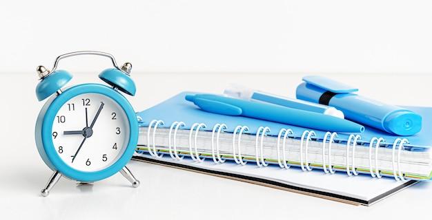Concepto de regreso a la escuela. reloj azul y suministros en blanco. copia espacio