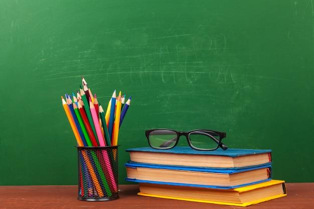 Concepto de regreso a la escuela con suministros de papelería y pizarra