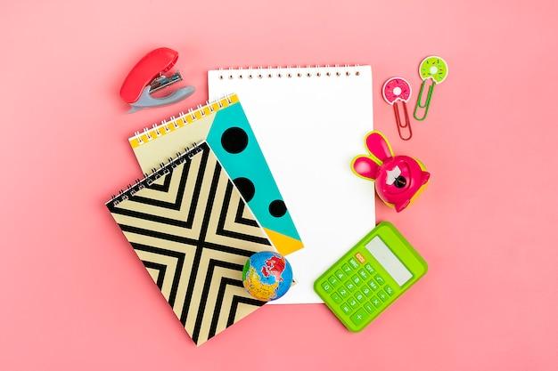 Concepto de regreso a la escuela. útiles escolares en rosa, plano.