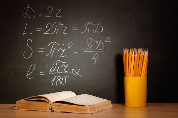 Concepto de regreso a la escuela. viejos libros de texto y lápices sobre un pupitre de madera frente a una pizarra negra con fórmulas matemáticas de la escuela.
