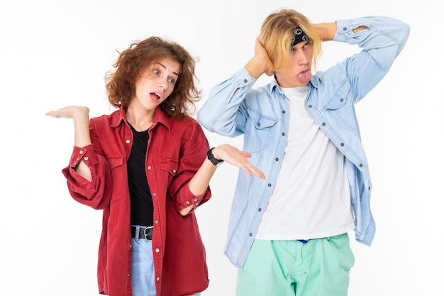 Concepto de relación. chico y chica en camisas casuales se ignoran cubriendo sus orejas sobre un fondo blanco.