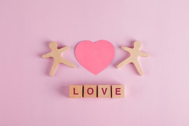 Concepto de relación con corazón cortado de papel, cubos de madera, modelos humanos en mesa rosa plana.