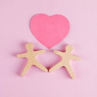Concepto de relación con corazón cortado de papel, modelos humanos de madera en mesa rosa plana.