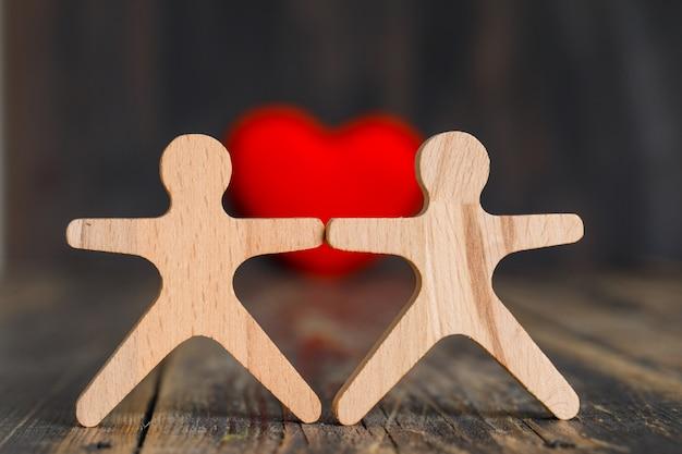 Concepto de relación con corazón rojo, figuras humanas de madera en vista lateral de la mesa de madera.