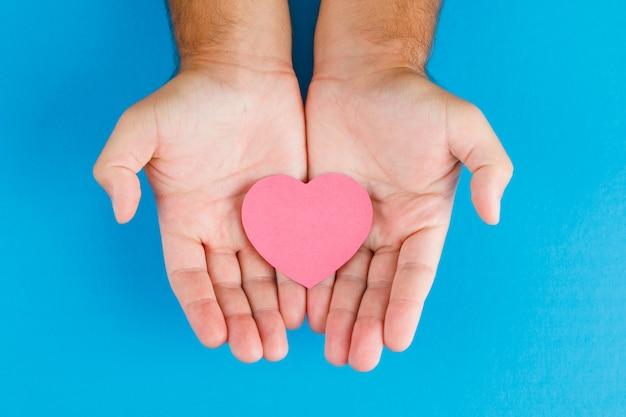 Concepto de relación en la mesa azul plano laical. manos sosteniendo papel cortado corazón.