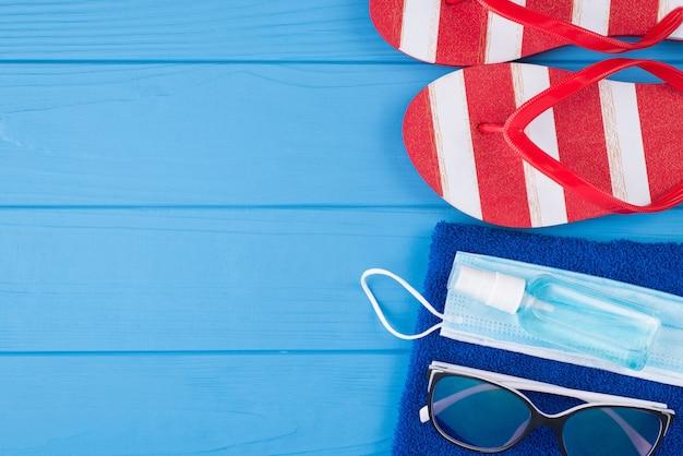 Concepto de relajación de cuarentena y verano. arriba, arriba, vista aérea, primer plano, foto, de, desinfectante, máscara, gafas de sol, toalla azul, y, flipflops, aislado, en, azul, de madera, plano de fondo, con, copyspace