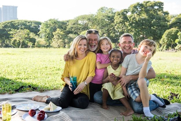 Concepto de la relajación de la unidad de la comida campestre de la familia al aire libre