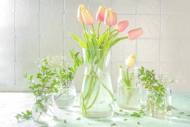 Concepto de renacimiento de la naturaleza de primavera. plantas verdes y flores silvestres de jardín en diferentes vasos y frascos sobre un fondo verde, interior de la casa, espacio de copia para texto composición floral de primavera.