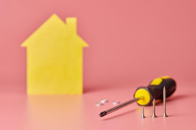 Concepto de renovación de la casa. reparación de viviendas y redecorado. tornillos y figura en forma de casa amarilla sobre rosa