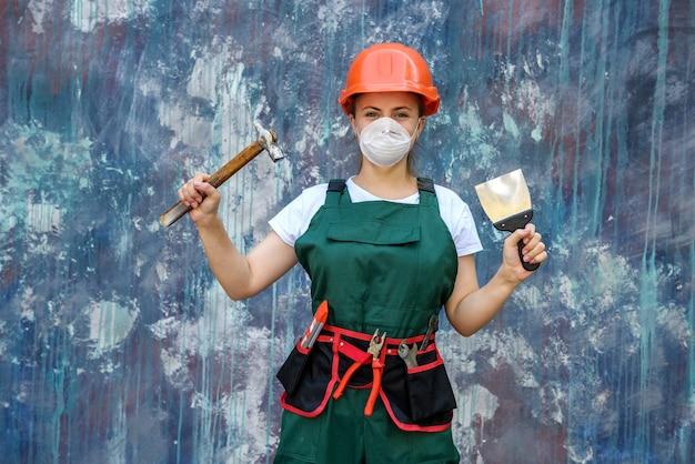 Concepto de renovación y remodelación. mujer con casco y máscara protectora posando con martillo y espátula