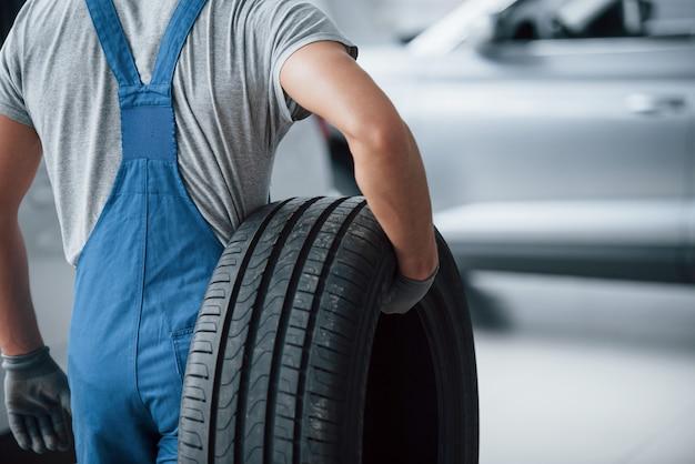 Concepto de reparación. mecánico sosteniendo un neumático en el taller de reparación. reemplazo de neumáticos de invierno y verano
