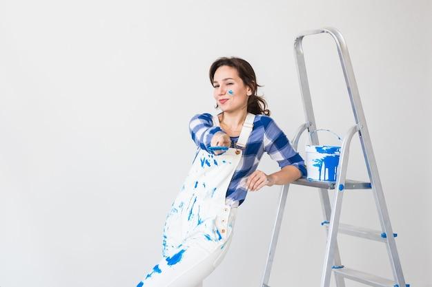 Concepto de reparación, renovación, nuevo hogar y personas - mujer joven haciendo redecoración sobre pared blanca