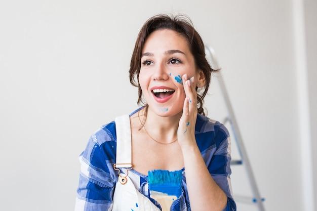 Concepto de reparación, renovación y personas - close up retrato de mujer joven atractiva con pintado