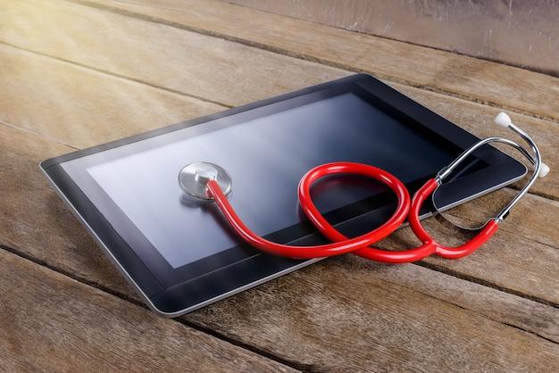 Concepto de reparación y servicio. tableta digital siendo diagnosticada con un estetoscopio.