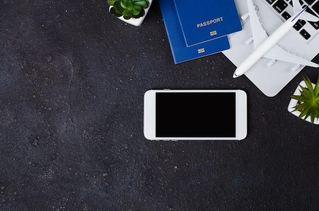 Concepto de reserva de viaje. modelo de computadora portátil, pasaportes, teléfono inteligente y avión sobre fondo oscuro.
