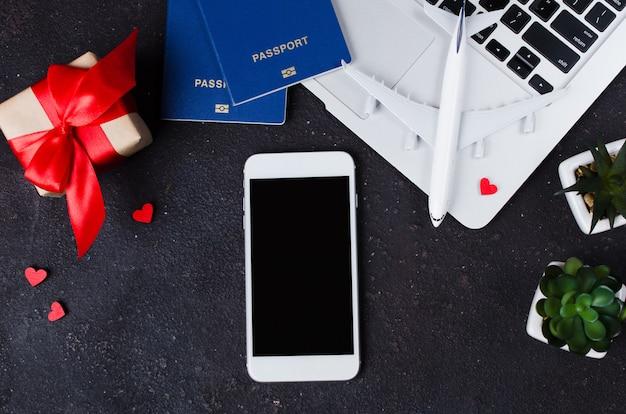 Concepto de reserva de viaje. teléfono inteligente, modelo de avión, computadora portátil, pasaportes y caja de regalo sobre fondo oscuro.