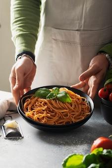 Concepto de restaurante. hombre cocinando espaguetis italianos con tomate y albahaca, imagen de enfoque selectivo