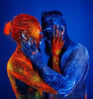 Concepto. retrato de un hombre y una mujer con barba pintados en polvo ultravioleta.