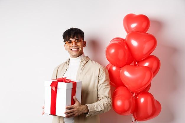 Concepto de romance y día de san valentín. el hombre enamorado prepara un regalo sorpresa para el amante, sosteniendo el presente en la caja y de pie cerca del gesto de corazones rojos, fondo blanco.