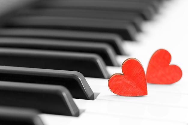 Concepto romántico con piano y corazones.