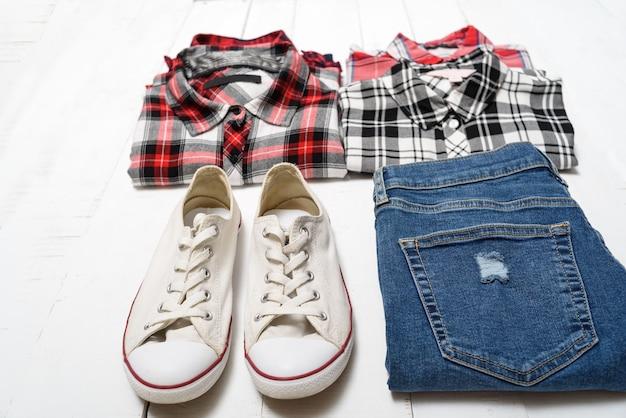 Concepto de ropa. camisas a cuadros, jeans y zapatillas blancas sobre un fondo de madera blanca.