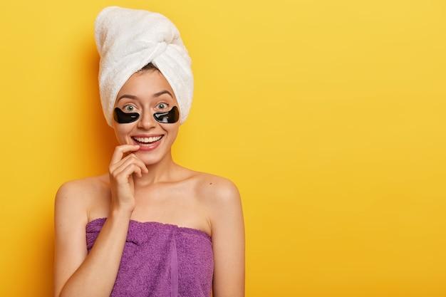 Concepto de rutina diaria de cuidado de la piel. hermosa mujer joven toca los labios con el dedo índice, sonríe ampliamente usa esponjas cosméticas para absorber nutrientes tiene una toalla de apariencia suave en la cabeza después de la ducha