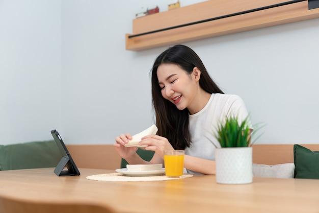 Concepto de sala de estar una mujer que usa su dispositivo electrónico para trabajar de forma remota en la acogedora habitación de la cafetería.