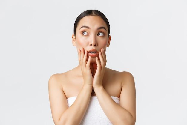 Concepto de salón de belleza, cosmetología y spa. abrumada chica asiática bonita en toalla mirando sorprendido y conmocionado en la esquina superior izquierda, tocando la cara limpia, de pie en la pared blanca.