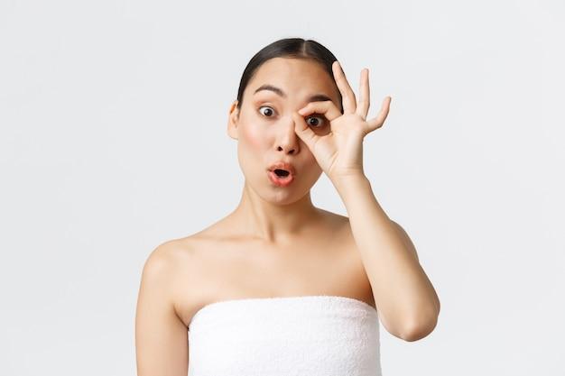 Concepto de salón de belleza, cosmetología y spa. chica asiática bonita sorprendida y curiosa en toalla de baño que parece intrigada a través de un gesto bien, diciendo wow, oferta de gran precio, pared blanca.