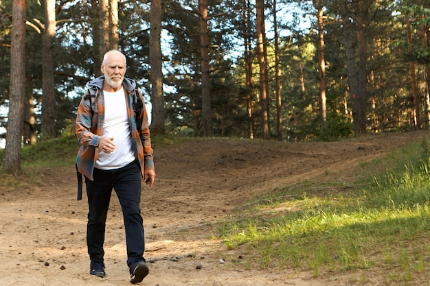 Concepto de salud, actividad, bienestar, edad y personas. hombre europeo barbudo activo autodeterminado de unos sesenta años caminando rápido mientras camina en el bosque de montaña, con mirada centrada en confianza