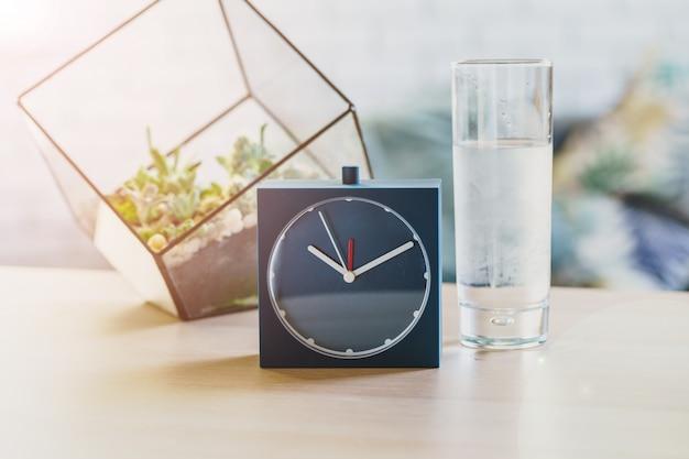 Concepto de salud del agua potable. despertador y vaso de agua sobre la mesa